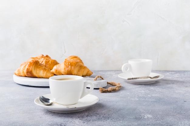 Tasses blanches de café et de croissants