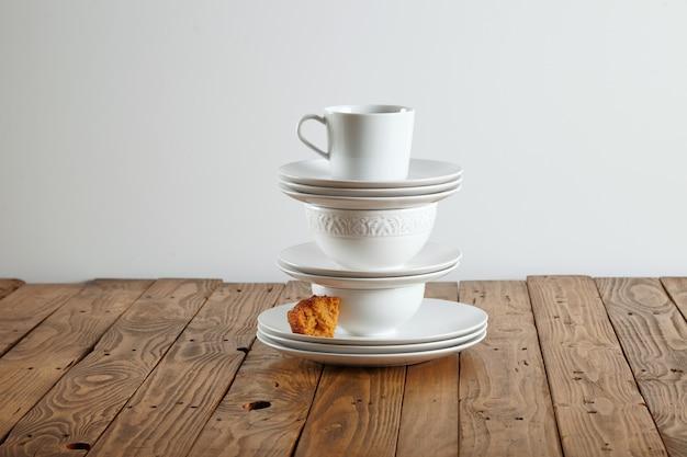 Tasses blanches similaires mais différentes perchées les unes sur les autres avec un petit morceau de génoise marron clair sur une soucoupe