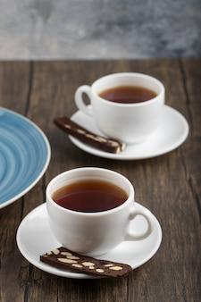 Tasses blanches de thé chaud avec un gâteau en tranches placé sur une table en bois.
