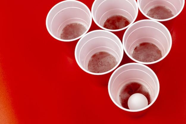 Tasses et boule en plastique sur fond rouge. jeu de beer pong