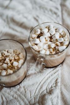 Tasses de cacao avec des guimauves près de la cheminée.