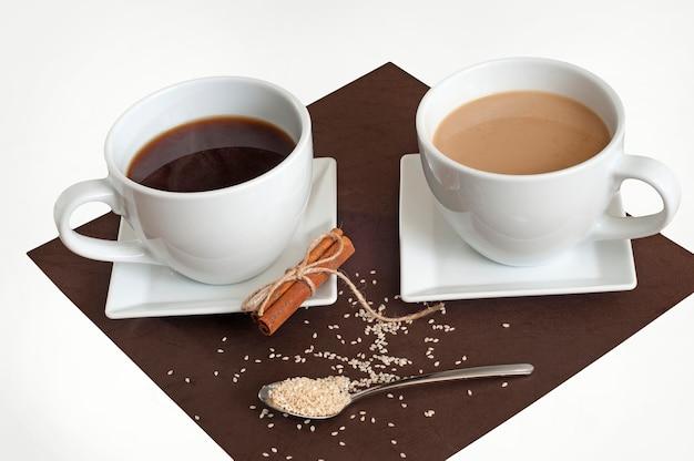 Tasses de café avec assortiment de soucoupes. cannelle et sésame.