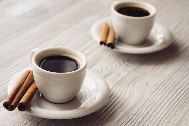 Tasses de café avec des bâtons de cannelle sur un fond en bois blanc