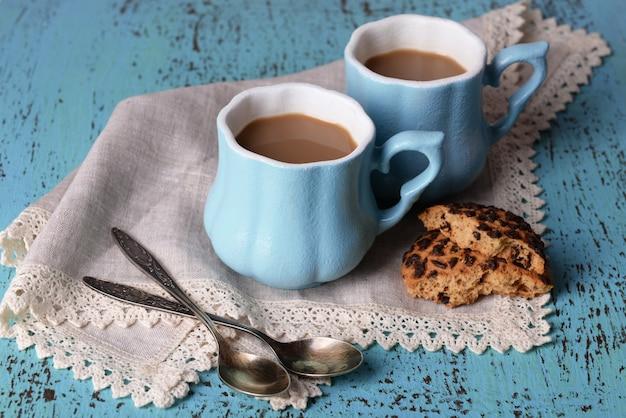Tasses de café avec des biscuits et serviette sur table en bois