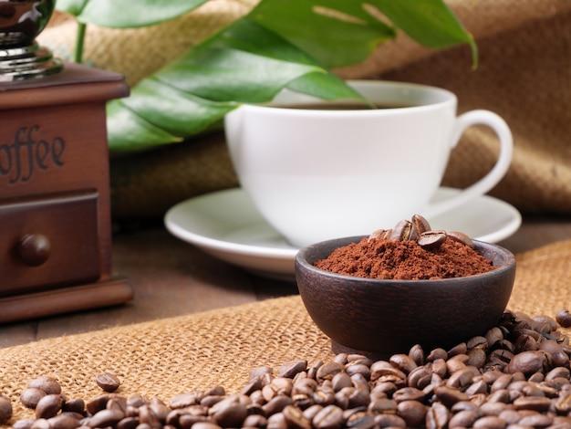 Tasses de café blanc café moulu à grains de café torréfié et monstera partent sur une table en bois avec surface en toile de jute