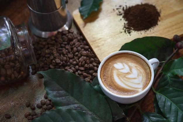 Des tasses à café blanches et des grains de café coulés sur une table en bois,