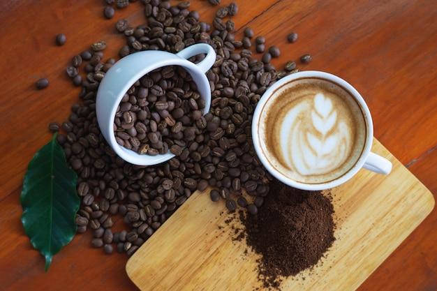 Tasses à café blanches et grains de café coulés sur une table en bois