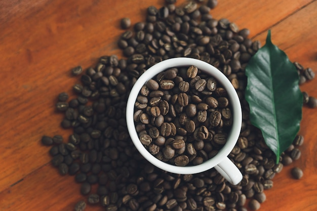 Des tasses à café blanches et des grains de café coulés sur une table en bois