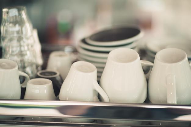 Des tasses à café blanches sont placées sur la machine à café.