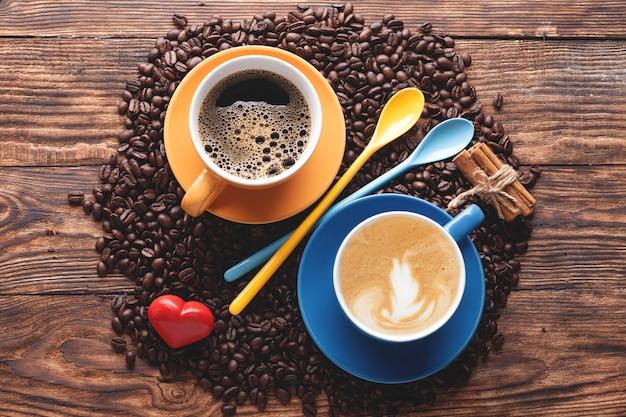 Tasses de café bleu et jaune, cuillères, haricots et coeur sur une table en bois
