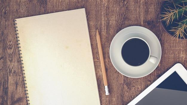 Tasses à café, cahiers, et le cactus sur la table en bois.
