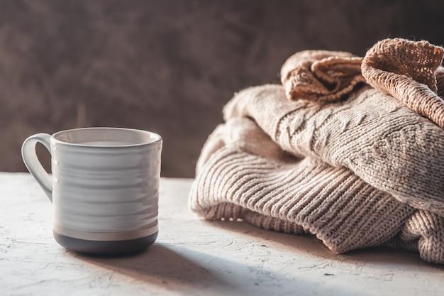 Tasses de café avec des chandails tricotés de couleur pastel chaude