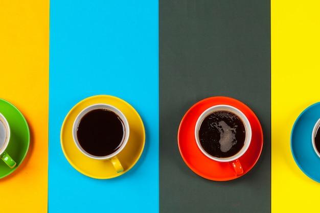 Tasses à café colorées et soucoupes sur vibrant coloré