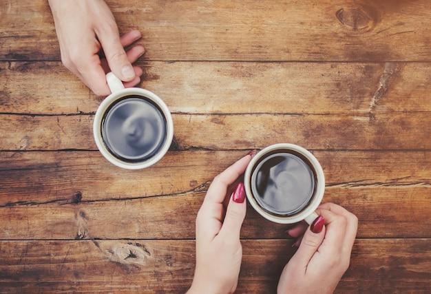 Tasses avec un café dans les mains des hommes et des femmes. mise au point sélective.