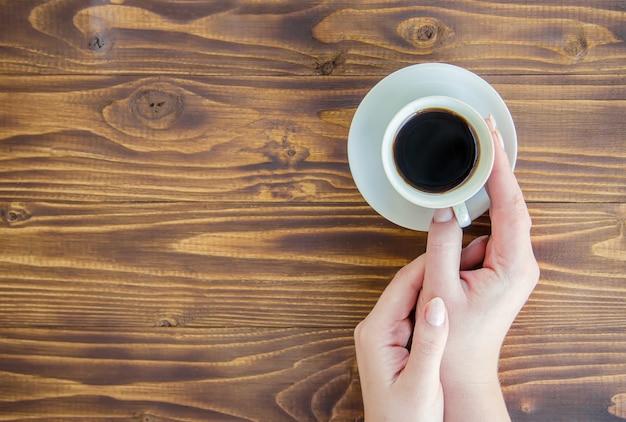 Tasses avec un café dans les mains des hommes et des femmes.