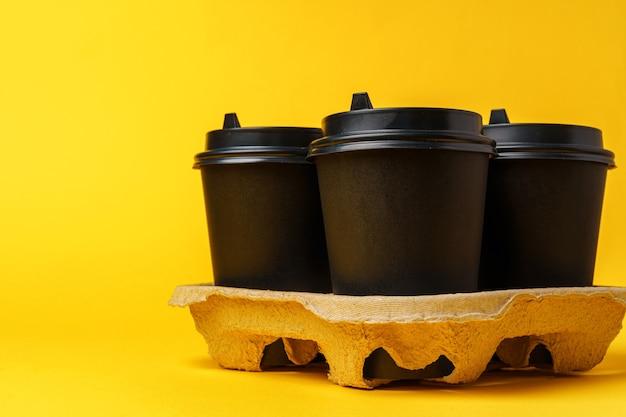 Tasses à café à emporter noires dans le support sur la table