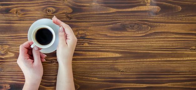 Tasses avec un café entre les mains des hommes et des femmes