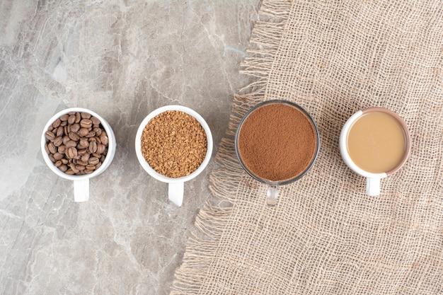 Tasses de café, grains de café et café moulu sur une surface en marbre. photo de haute qualité