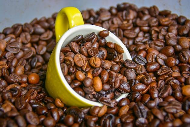 Tasses à café jaunes et grains de café arabica qui ont été traités thermiquement jusqu'à ce qu'ils soient prêts à être moulus.
