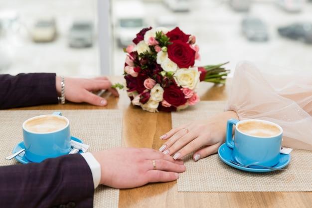 Tasses de café et les mains des jeunes mariés sur la table