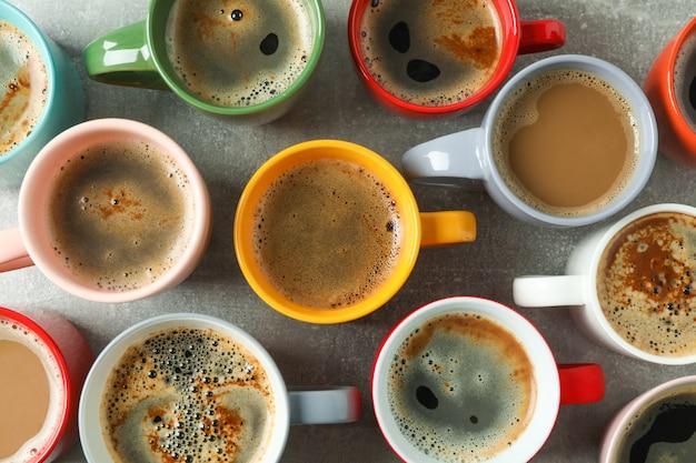 Tasses de café multicolores sur table grise en arrière-plan