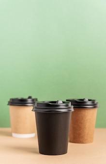 Tasses à café en papier à emporter noir maquette sur fond vert et marron