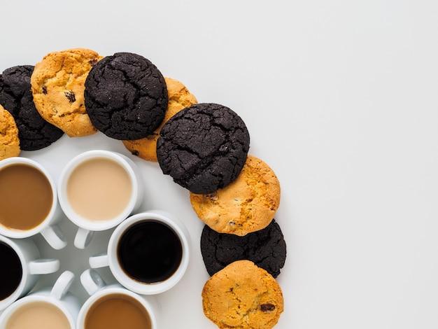 Tasses à café placées dans un cercle et différents cookies