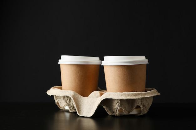 Tasses à café respectueuses de l'environnement sur fond noir, espace pour le texte