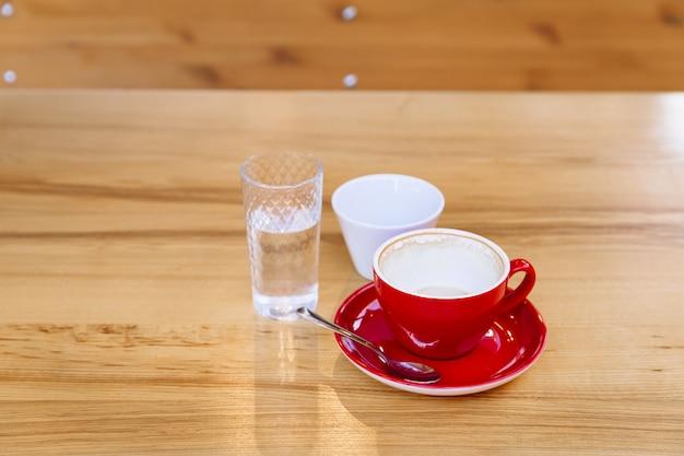 Des tasses à café sales, un cappuccino et un verre d'eau se dressent sur une table en bois.