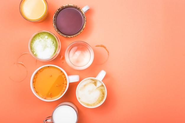 Tasses de café, thé, jus et eau. boissons du matin pour différentes préférences. vue de dessus.
