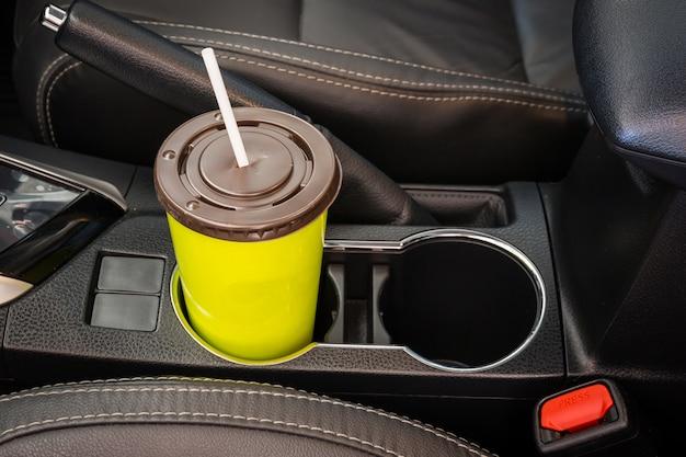 Tasses à café ou à thé vert posées sur la console du véhicule à l'intérieur d'une voiture de luxe moderne