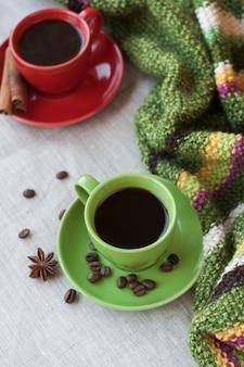 Tasses de café vertes et rouges avec des grains de café, des étoiles d'anis et des bâtons de cannelle
