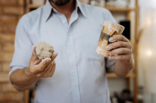 Tasses en céramique. bricoleur professionnel créatif se sentant très occupé lors de la fabrication de tasses en céramique marron