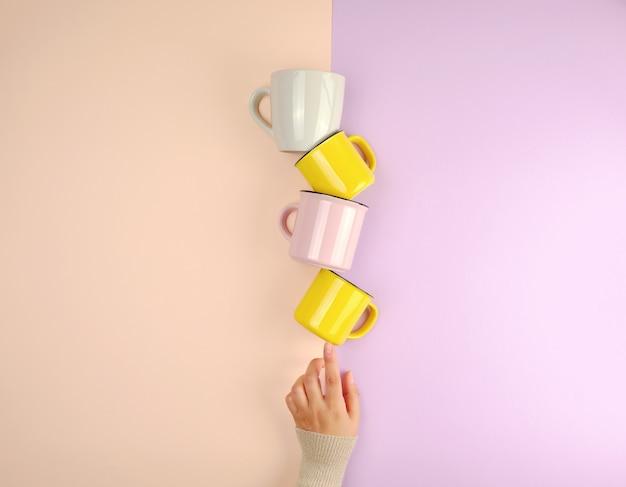 Les tasses en céramique empilées sont soutenues par une main féminine