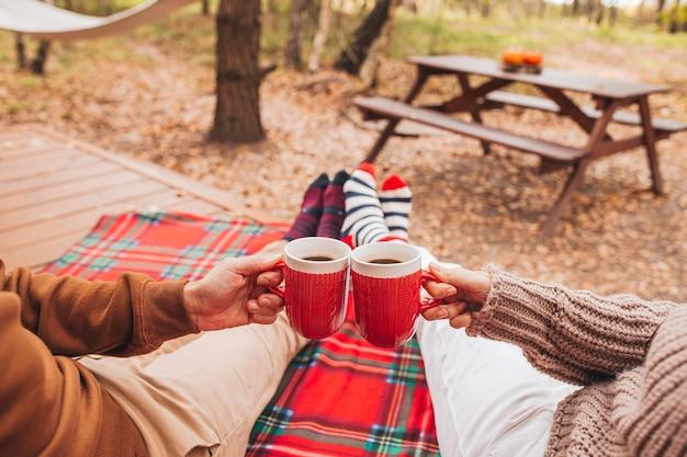 Tasses chaudes de thé réchauffant les mains humaines en pull en laine sur la terrasse au jour d'automne