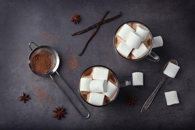 Tasses de chocolat chaud avec des guimauves sur une table grise