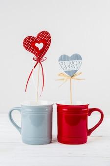 Tasses avec coeurs d'ornement sur baguettes