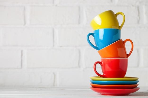 Tasses colorées sur le blanc d'un mur de briques. avec copie espace. horizontal. mise au point sélective.