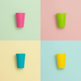 Tasses colorées sur différents fonds pastel.