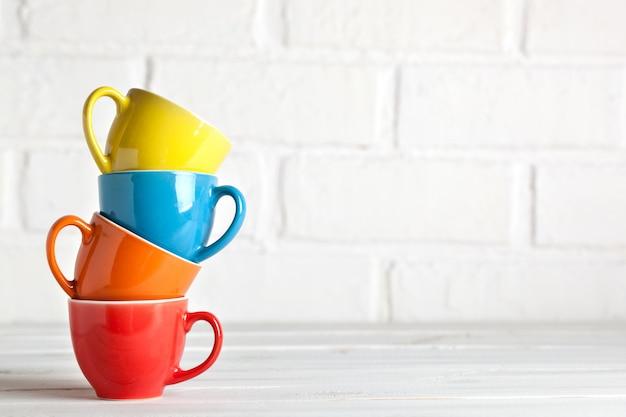 Tasses colorées sur fond blanc d'un mur de briques. fond avec espace copie. horizontal. mise au point sélective.
