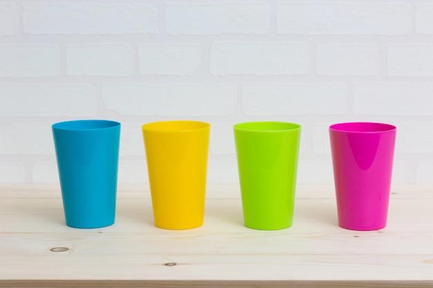 Tasses colorées sur le mur de briques blanches de table en bois.