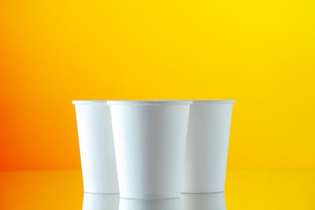Tasses à eau en papier vue de face sur mur jaune