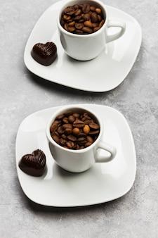 Tasses à espresso blanches remplies de grains de café et de chocolat en forme de coeur sur fond clair
