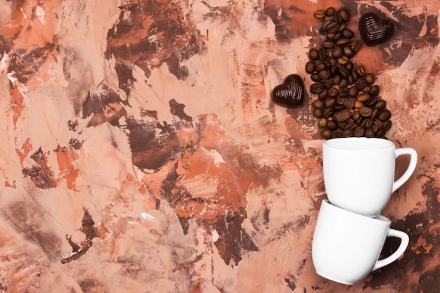 Tasses à espresso blanches remplies de grains de café et de chocolat en forme de coeur sur fond marron. vue de dessus, espace copie. contexte alimentaire.