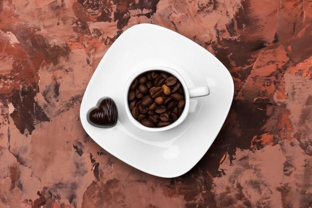 Tasses à espresso blanches remplies de grains de café et de chocolat en forme de cœur. vue de dessus