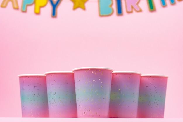 Tasses de fête rose avec guirlande de joyeux anniversaire sur fond rose