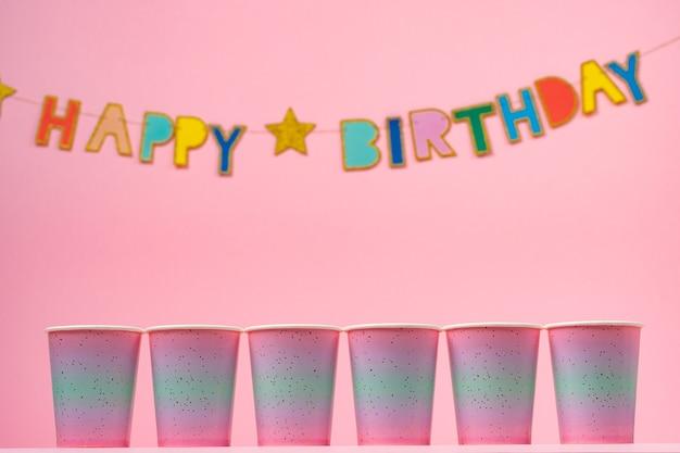 Tasses de fête rose avec guirlande de joyeux anniversaire sur rose close up