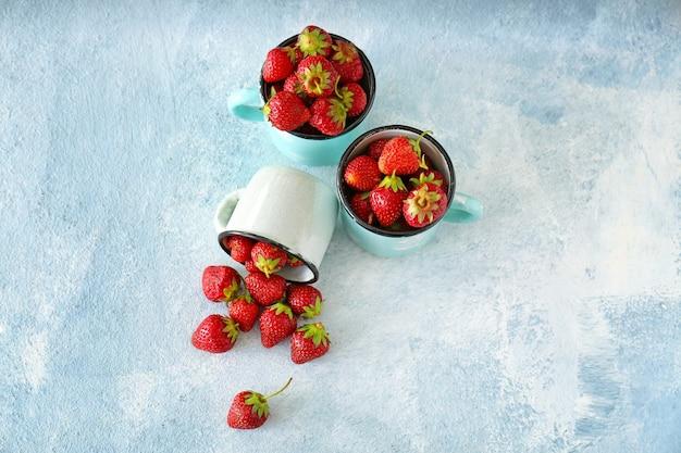 Tasses avec fraise rouge mûre sur table des couleurs
