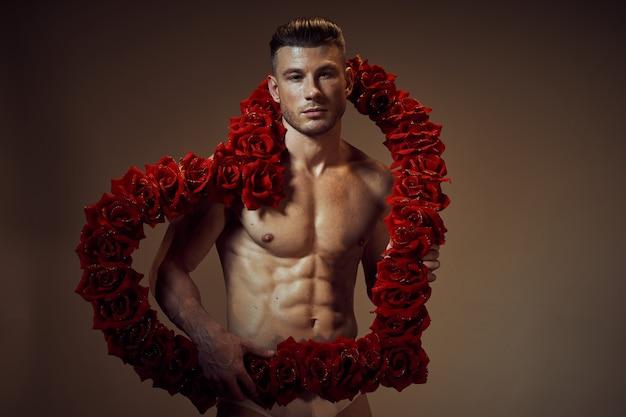 Tasses d'homme sur le cadeau en forme de coeur de fleurs de corps musclé