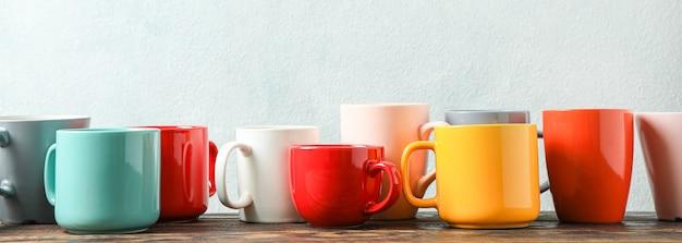 Tasses multicolores sur table en bois sur fond clair